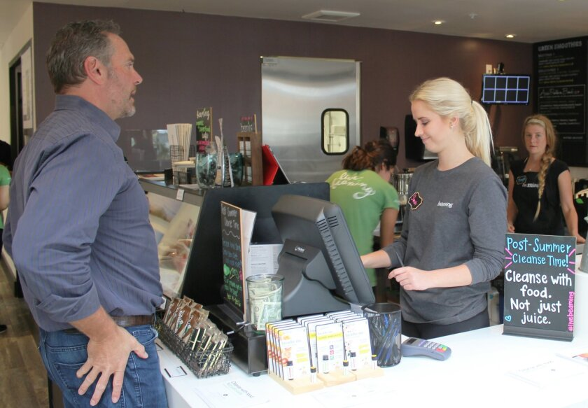 Visitors sample the vegan, low-glycemic juices and food at Beaming, which bills itself as an 'organic superfood café.' Founder Lisa Odenweller opened her fifth Southern California location Sept. 14 in the La Plaza La Jolla shopping center at Wall Street and Girard Avenue.