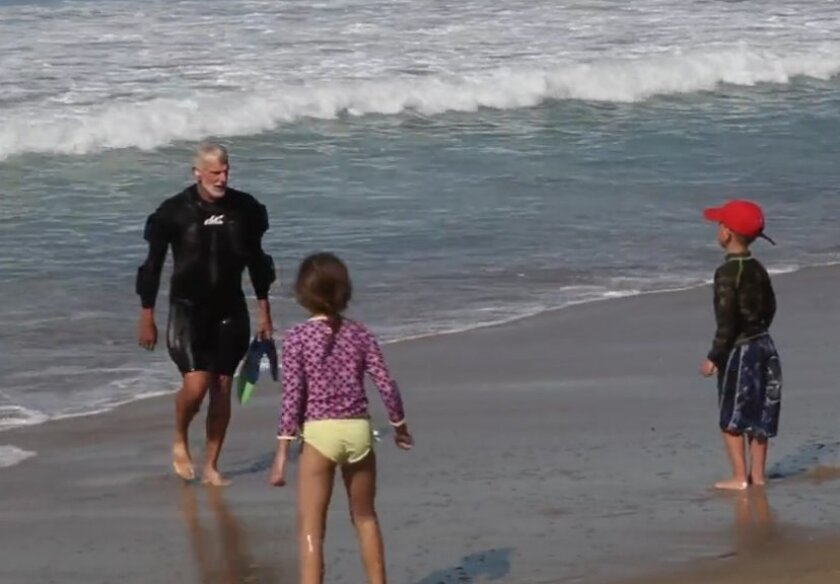 Rich Ganzer walks out of the ocean wearing a WaveWrecker wetsuit as two children quizzically look on.