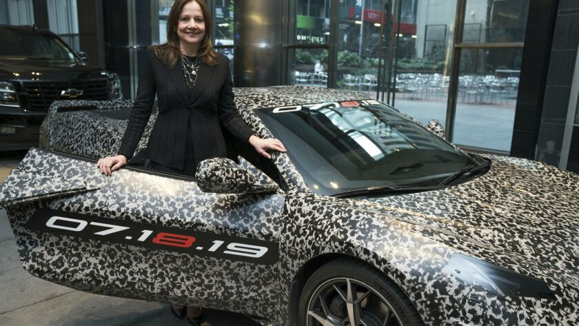 This image provided by General Motors shows GM chairman and CEO Mary Barra standing by a camouflaged