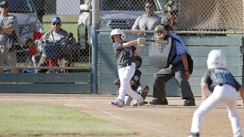 Costa Mesa American Little League's Parker Stringham bats in a run against Seaview in an 8- and 9-ye