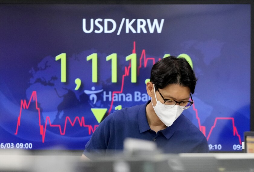 A currency trader stands near the screen showing the foreign exchange rate between U.S. dollar and South Korean won at the foreign exchange dealing room in Seoul, South Korea, Thursday, June 3, 2021. Shares have advanced in Asia Thursday after a day of modest gains on Wall Street led by buying of energy and technology stocks. Oil prices also rose. (AP Photo/Lee Jin-man)