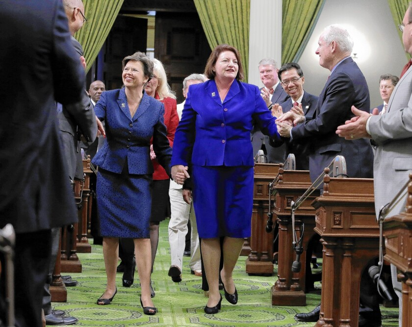Assembly Speaker-elect Toni Atkins (D-San Diego), right, walks hand in hand with her spouse, Jennifer LeSar, to the rostrum of the Assembly where she took the oath of office as Assembly speaker at the Capitol in Sacramento.