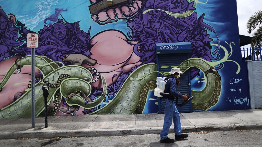 Larry Smart, a mosquito control inspector, uses an insecticide fogger to kill mosquitoes in Miami's Wynwood neighborhood.