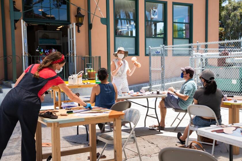 Stace Fulwiler Wood (en medio) enseña un taller al aire libre sobre la creación de sandalias de cuero