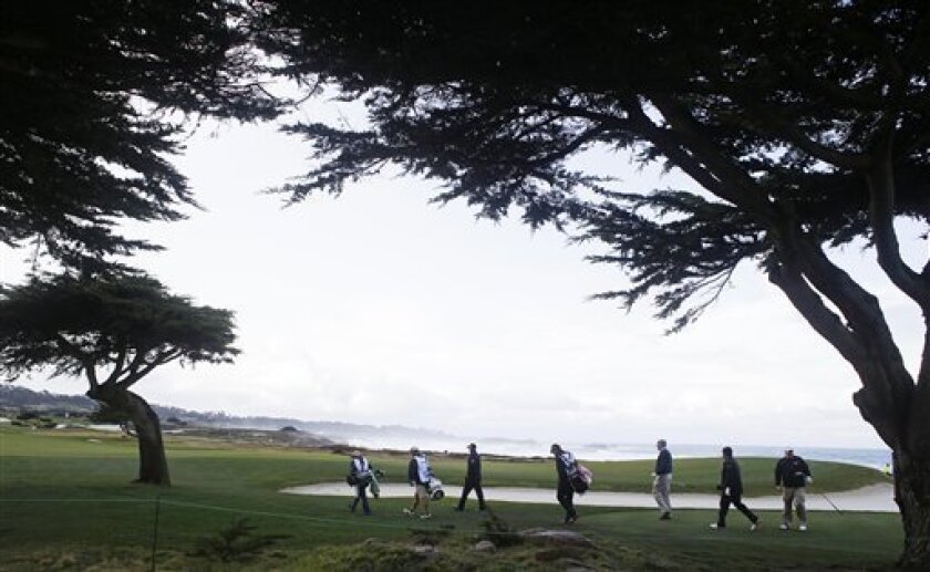 The playing group of Ted Potter Jr. and John Daly make their way toward the 12th fairway of the Monterey Peninsula Country Club Shore Course during the second round of the AT&T Pebble Beach Pro-Am golf tournament on Friday, Feb. 8, 2013 in Pebble Beach, Calif. (AP Photo/Eric Risberg)