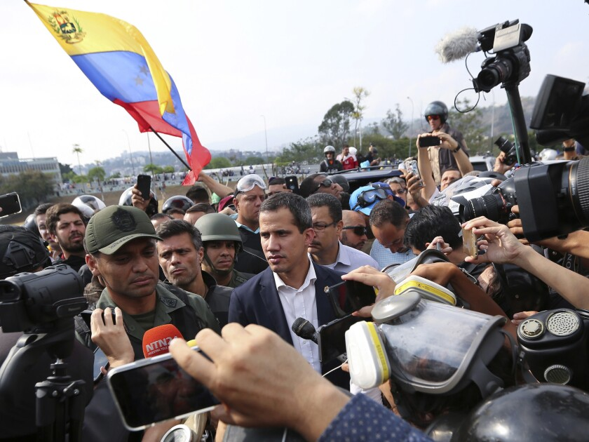 Venezuela's opposition leader and self-proclaimed president Juan Guaido, center, stands with an unid