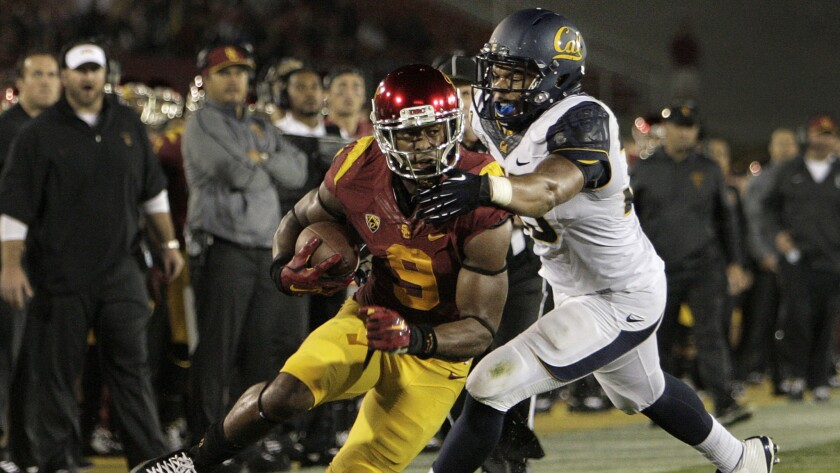 USC wide receiver JuJu Smith avoids being tackled by California defensive end Noah Westerfield on an eight-yard reception during the Trojans' win on Thursday.