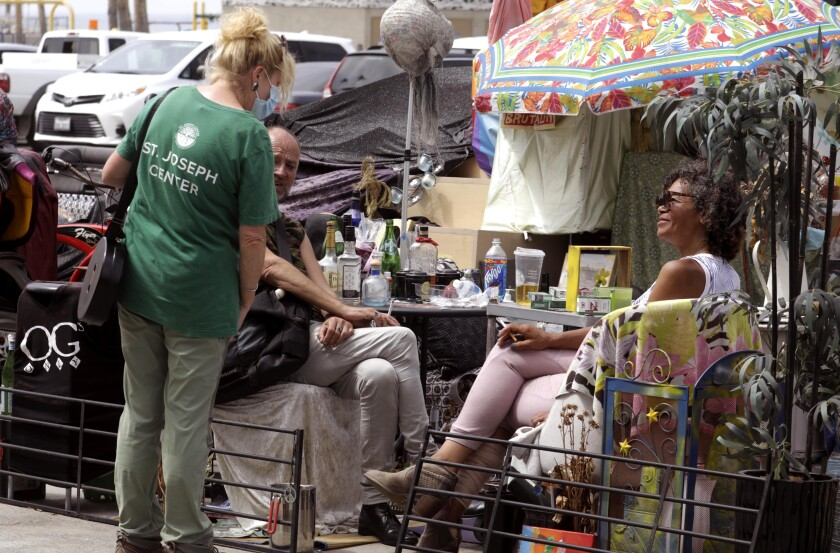 A worker with the St. Joseph Center talks with a homeless couple along Ocean Front Walk in Venice on July 7.