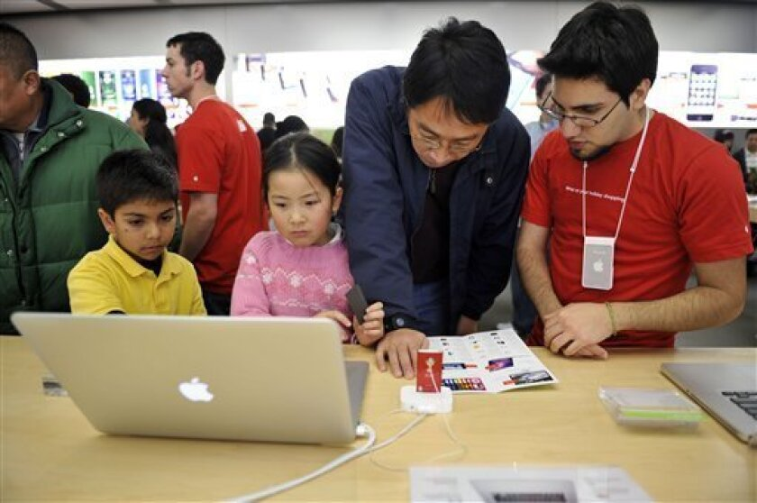 FILE - In this Nov. 27, 2009 file photo, Apple Store employee Rouzbehh Ohasemi, right, helps out holiday shoppers Frank Wang, Danya Wang, 7, and Abhinav Morbad, 7, as they check out a MacBook Pro at the Apple Store in Valley Fair Shopping Centre in San Jose, Calif. (AP Photo/Russel A. Daniels, file)