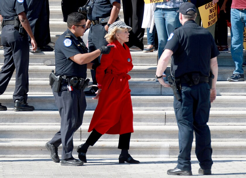 Jane Fonda, with hands cuffed behind her back, being led by a police officer near the Capitol steps.