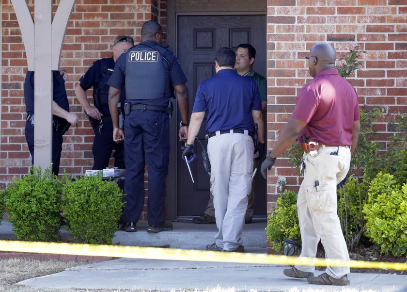Tulsa police gather at the front entrance of a home as they investigate after the bodies of four people were found in Tulsa, Okla., Wednesday, April 1, 2015. Tulsa police said the bodies included two young boys and were found in the home after a man and a woman missed two days of work. (AP Photo/Tulsa World, Michael Wyke) ONLINE OUT; KOTV OUT; KJRH OUT; KTUL OUT; KOKI OUT; KQCW OUT; KDOR OUT; TULSA OUT; TULSA ONLINE OUT
