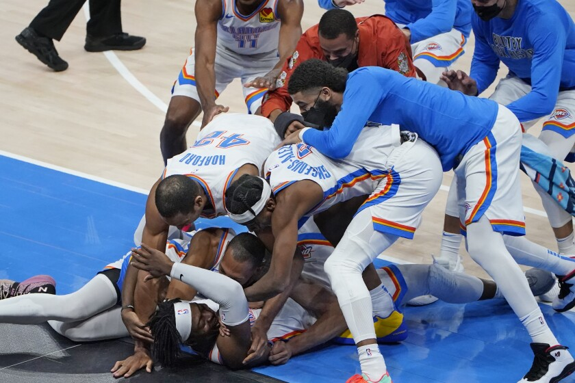 Oklahoma City Thunder forward Luguentz Dort, bottom, is mobbed by teammates after hitting the game-winning shot in an NBA basketball game against the San Antonio Spurs, Wednesday, Feb. 24, 2021, in Oklahoma City. (AP Photo/Sue Ogrocki)
