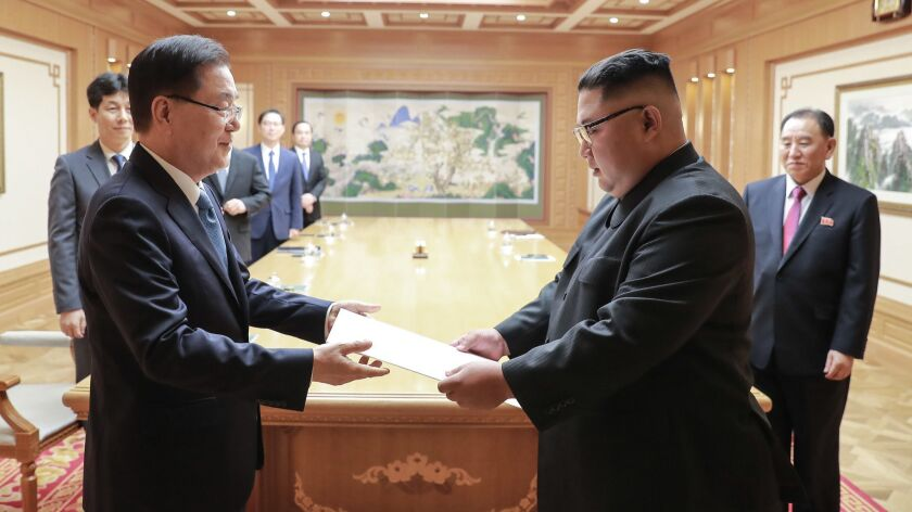 North Korean leader Kim Jong Un, right, receives a letter from South Korean President Moon Jae-in, delivered by Moon's national security advisor Chung Eui-yong, left, on Sept. 5 in Pyongyang.