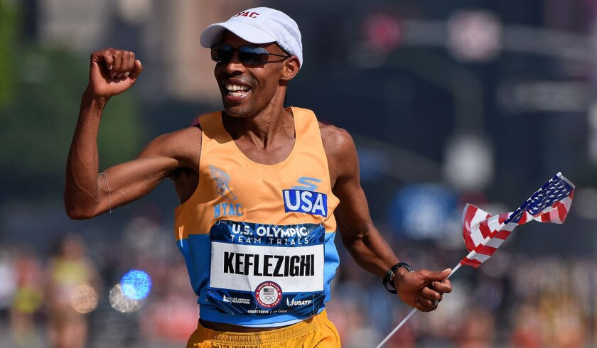 Meb Keflezighi celebrates as he approaches the finish line during the U.S. Olympic marathon trials.