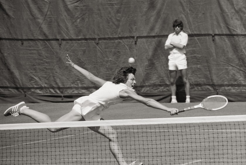 Wearing all white, Billie Jean King runs and reaches with a tennis racket to hit a shot at the net while a ball boy watches.