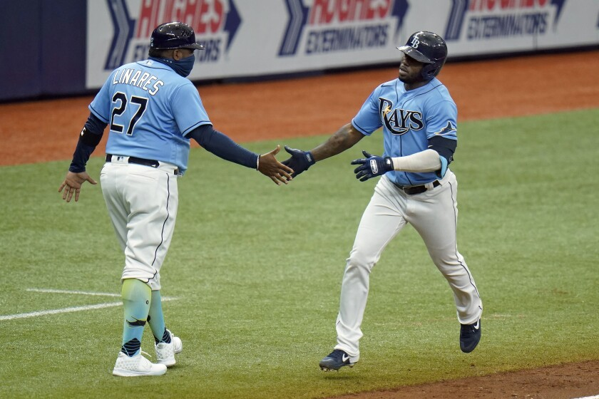 Tampa Bay Rays' Randy Arozarena shakes hands with third base coach Rodney Linares (27) after his solo home run off Miami Marlins starting pitcher Trevor Rogers during the sixth inning of a baseball game Sunday, Sept. 6, 2020, in St. Petersburg, Fla. (AP Photo/Chris O'Meara)