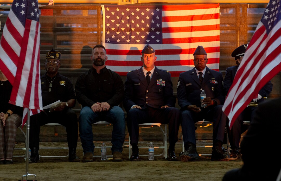 Men sit in chairs in front of a U.S. flaf. Some are in military uniform.