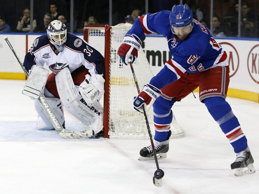 New York Rangers left wing Rick Nash (61) looks to pass with Columbus Blue Jackets goalie Curtis McElhinney (30) keeping a close eye on him in the second period of an NHL hockey game at Madison Square Garden in New York, Sunday, Feb. 22, 2015. (AP Photo/Kathy Willens)