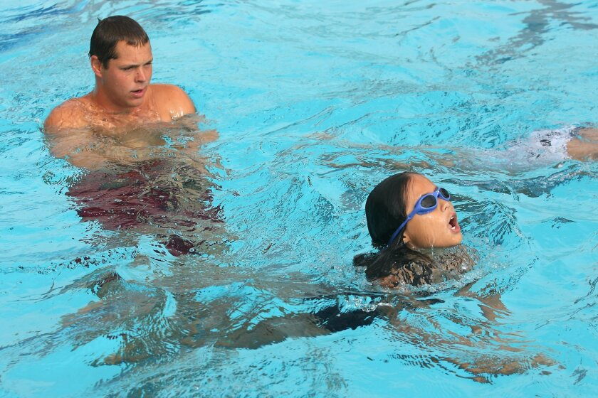 Swim instructor Michael Lutz looks on as 9-year-old Yoo Seo-Ra practices her strokes at the Washington Park Pool in Escondido.