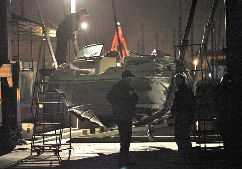 Law enforcement officials examine the pleasure boat struck by the Coast Guard boat on Dec. 20, 2009.