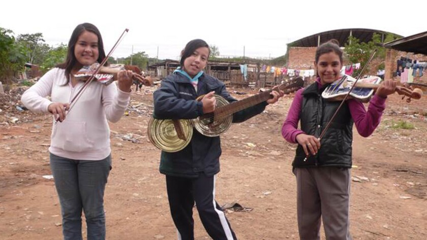 "Left to right, Maria Rios, Noelia Rios and Tania Vera Hertz holding recycled instruments in the documentary ""Landfill Harmonic."""