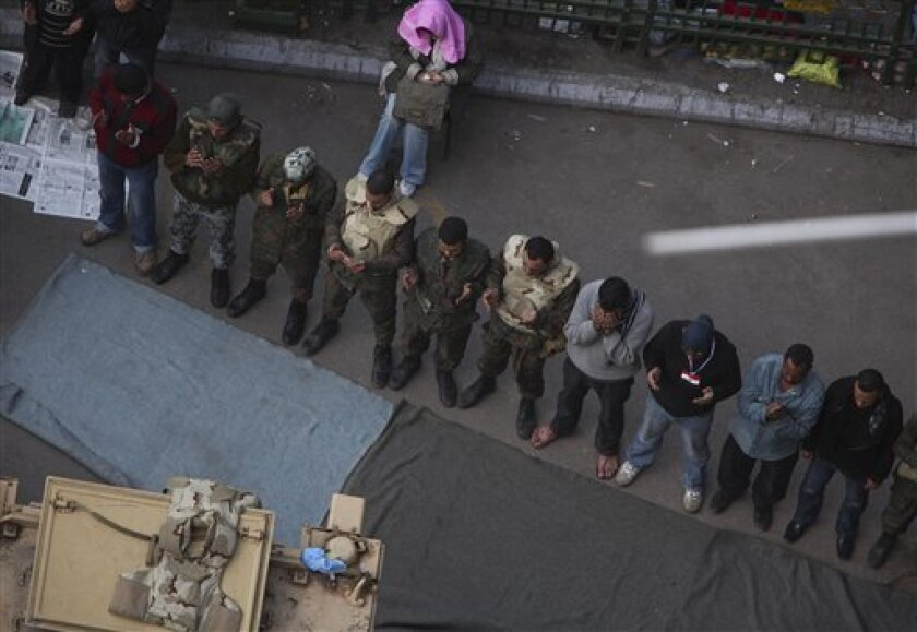 Anti-government protesters make traditional Muslim Friday prayers along side Egyptian soldiers at the continuing demonstration in Tahrir Square in downtown Cairo, Egypt Friday, Feb. 11, 2011. (AP Photo/Tara Todras-Whitehill)