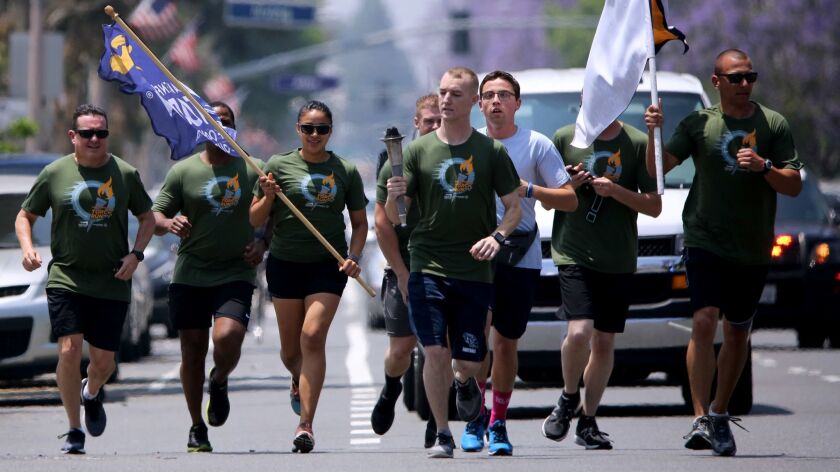 Glendale Police officers carry the torch on Glenoaks Blvd., during the Special Olympics Torch run in
