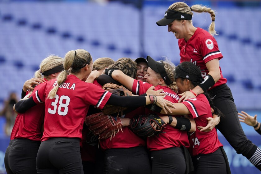 Members of team Canada celebrate after defeating Mexico in a softball game at the 2020 Summer Olympics