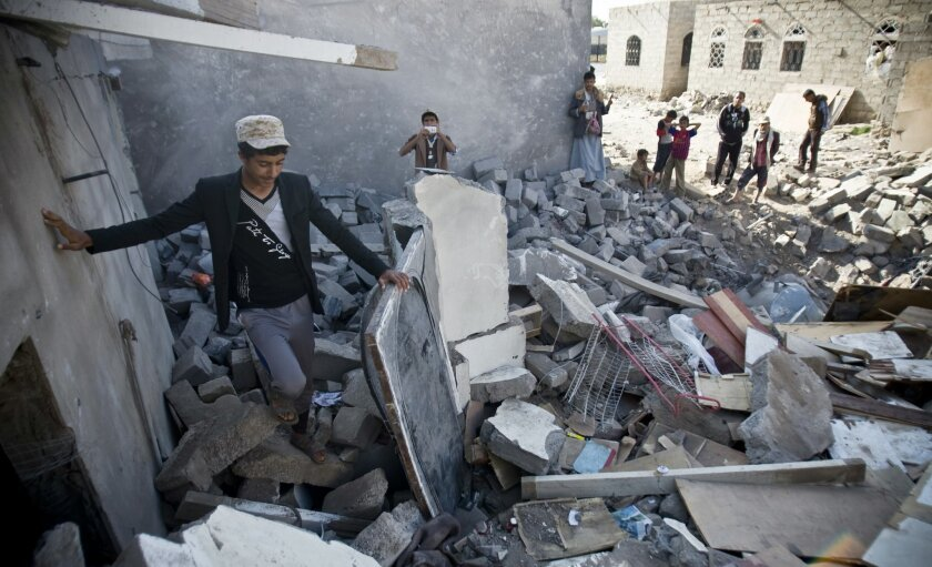 FILE - In this Tuesday, March 31, 2015 file photo, people gather near the rubble of houses destroyed by Saudi airstrikes near the airport in Sanaa, Yemen. Saudi Arabia and its allies plan an ambitious ground offensive on multiple fronts in Yemen. It may be inevitable if they want to defeat Iranian-
