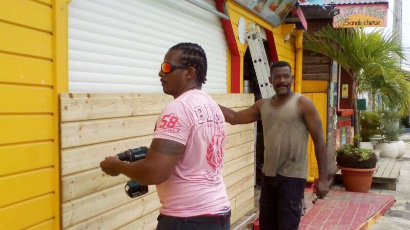 Men board up buildings ahead of Hurricane Maria in Sainte-Anne on the French Caribbean island of Gua