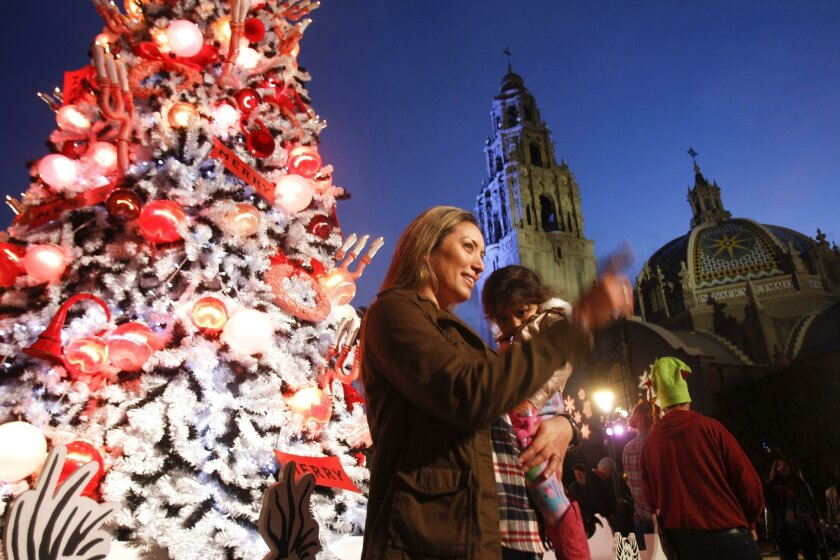 SAN DIEGO, CA, December 4, 2015 | Erica Durazo poses for a picture while holding her daughter Kassandra, 2, while in front of the Christmas tree next to the Old Globe Theater during December Nights at Balboa Park in San Diego on Friday. | -Mandatory Photo Credit: Photo by Hayne Palmour IV/San Diego