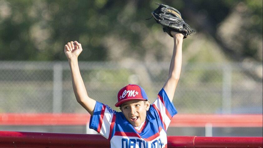 Costa Mesa National Little League's Xavier Shoda reacts after robbing a homerun from Costa Mesa Amer