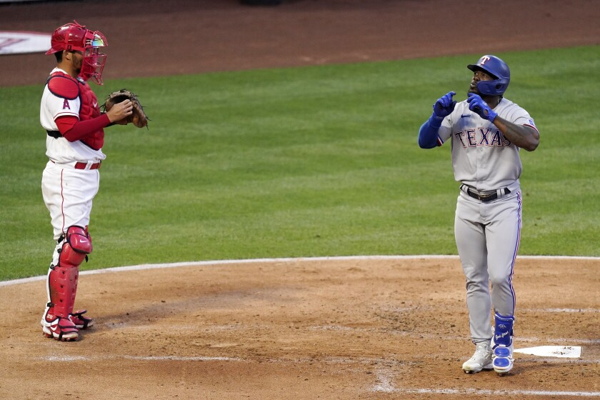 Texas Rangers' Adolis Garcia celebrates as he scores after hitting a solo home run as Angels catcher Kurt Suzuki watches.