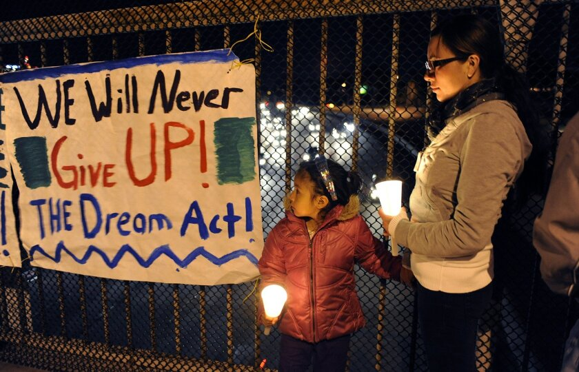 Saray Flores, 22, and her niece Layla Flores, 3, hold candles during a candlelight vigil for the DREAM Act on Park Boulevard Monday. The DREAM Act (Development, Relief and Education for Alien Minors) could come up for vote before Congress soon.   K.C. Alfred • U-T