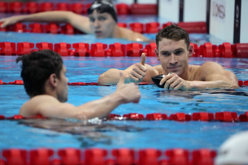 Ryan Murphy gives a thumbs up to Evgeny Rylov in the pool at the Tokyo Olympics.
