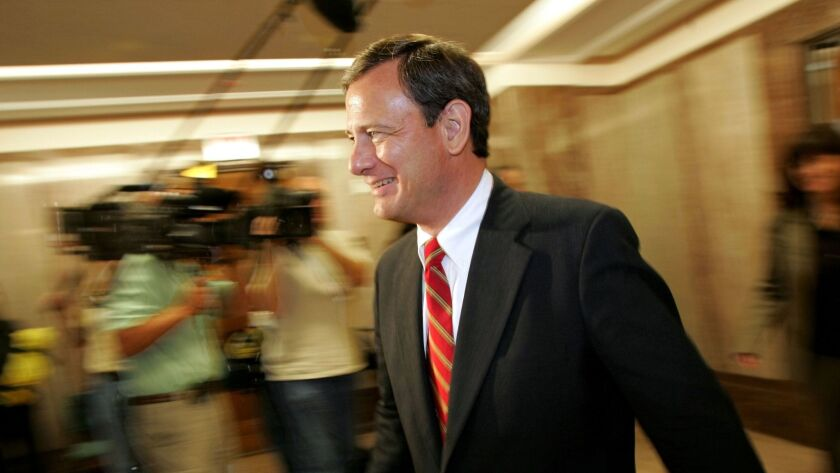 U.S. Supreme Court nominee John Roberts walks past members of the press following his meeting with S