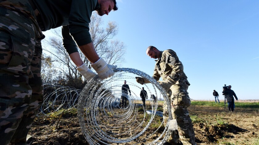 Slovenian soldiers set up barbed-wire fences on the Slovenian-Croatian border near Rakovec.