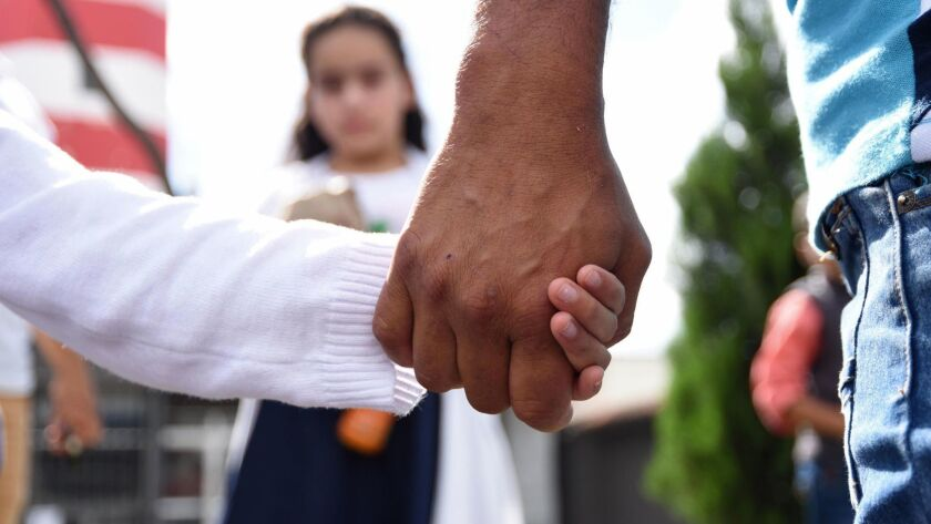 A man holds his daughter's hand after picking her and his wife up at a Guatemalan air force base on July 10, 2018. His wife and daughter had been deported from the United States.