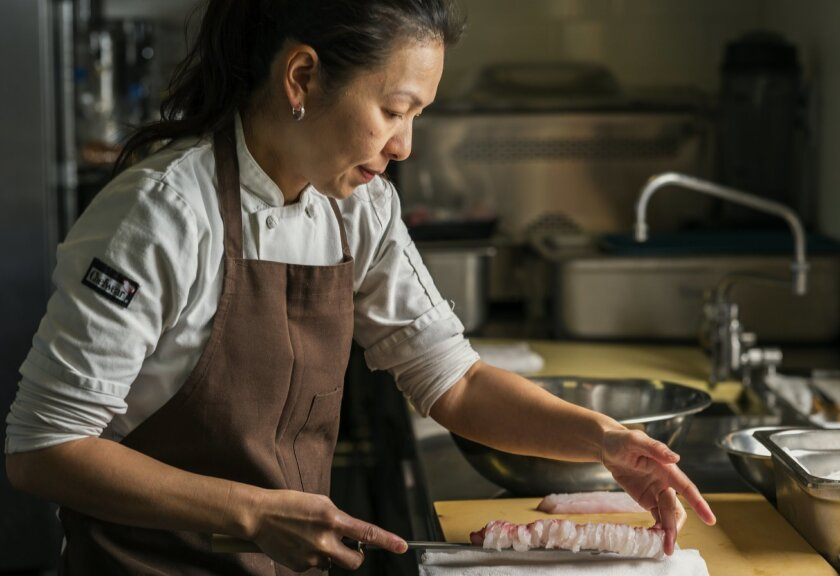 """In this Thursday, April 9, 2015 photo, chef Niki Nakayama cuts fish at her n/naka restaurant in Los Angeles. Chef Niki Nakayama is one of just six chefs to be profiled on Netflix's first homegrown documentary series, """"Chef's Table,"""" which features some of the most innovative chefs cooking today. (AP Photo/Damian Dovarganes)"""