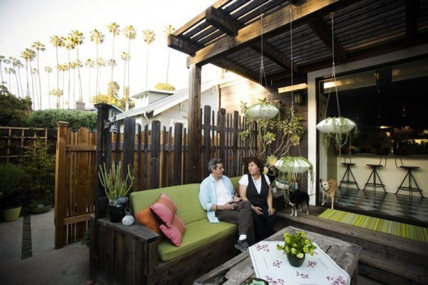 """Annette Gutierrez, pictured with husband Gustavo, created an outdoor great room as an extension of the indoor kitchen. """"I wanted it to feel like my front living room so you can walk out and just plop down and relax,"""" Gutierrez said. """"We use it all the time."""" For a tour of her outdoor living areas, keep clicking."""