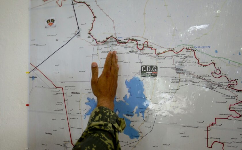 In this Sept. 5, 2014 photo, a soldier points out the border area, shared by the states of Texas and Tamaulipas, under gang influence on a map at a military base in Ciudad Mier, Tamaulipas state, Mexico. As Mexico prepares to develop rich shale fields along the Gulf Coast, and attract foreign inves
