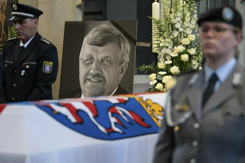 FILE-In this June 13, 2019 file photo a picture of Walter Luebcke stands behind his coffin during the funeral service in Kassel, Germany. German investigators have carried out raids on dozens of people suspected of posting hate messages about a regional politician from Chancellor Angela Merkel's party who was killed last year. Walter Luebcke, who led the regional administration in the central Kassel region, was shot on June 1, 2019. (Swen Pfoertner/dpa via AP, file)