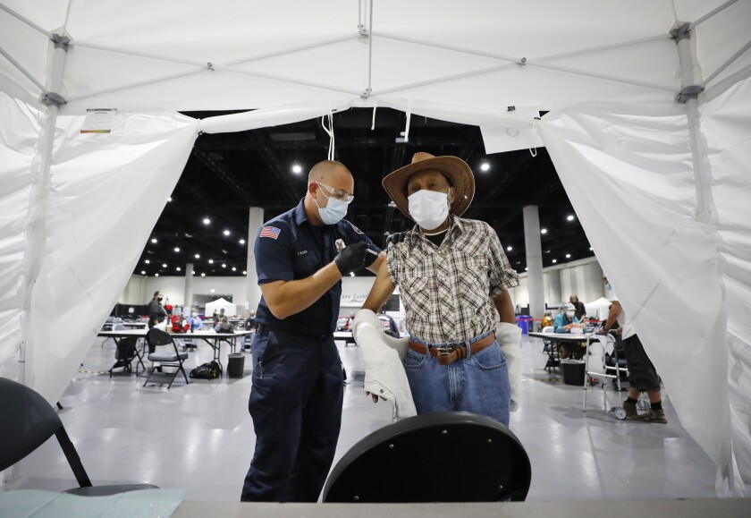San Diego firefighter Tim Olson administers a COVID-19 vaccine to Rudy Rowe at San Diego Convention Center homeless shelter.