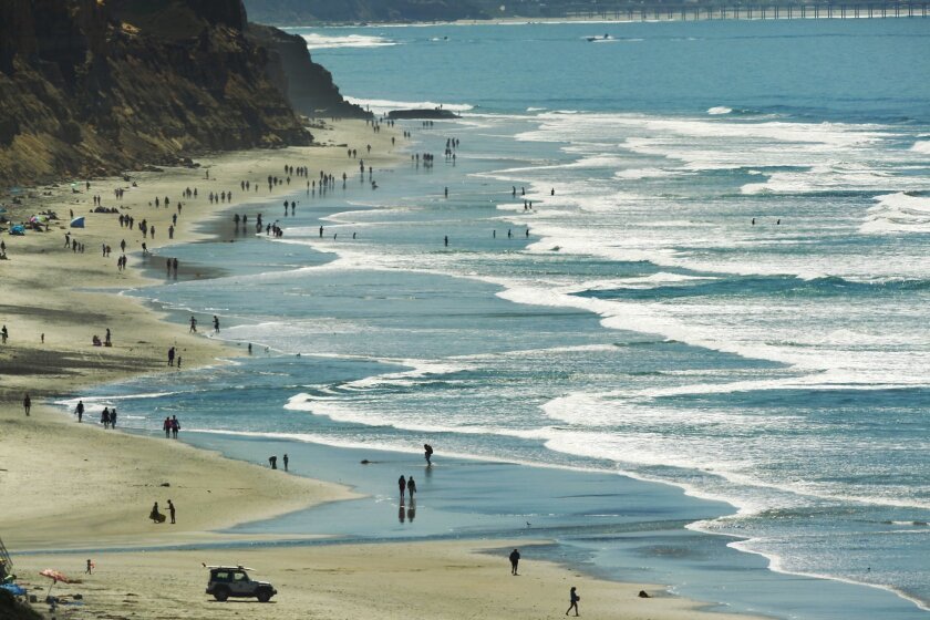 Beach goers enjoying a hot afternoon at Torrey Pines State Beach in March. Torrey Pines is one of many state beaches where visitors soon won't be able to shower off.