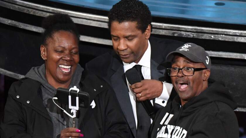 "Actor Denzel Washington, center, greets tourists Gary Alan Coe, aka ""Gary From Chicago,"" and his fiancée, Vickie Vines, at the Academy Awards on Sunday. Coe had recently been released from prison."