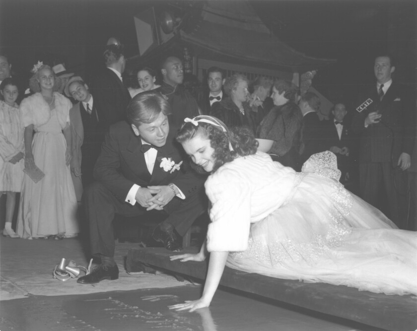Mickey Rooney watches Judy Garland put her handprint in cement at Grauman's Chinese Theatre on Oct. 25, 1939.