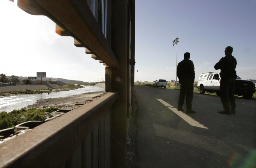 Border Patrol agents stand near their vehicles, on the south side of the concrete Tijuana River channel, just west of the San Ysidro border crossing in this view looking west. On the other side of the river, at left, is Tijuana.