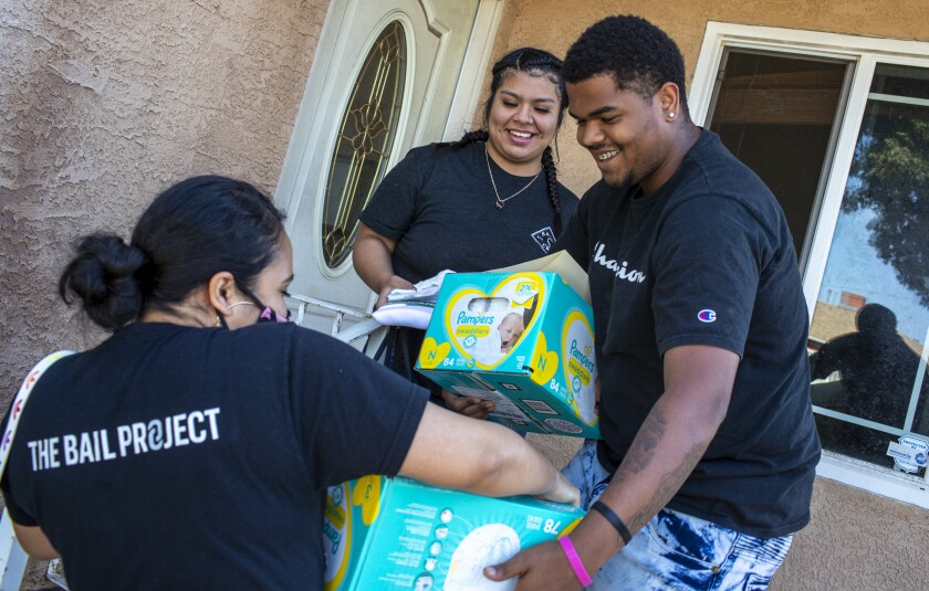 Priscilia Martinez, left, of the Compton chapter of the Bail Project delivers supplies to Tomajae Tolliver.
