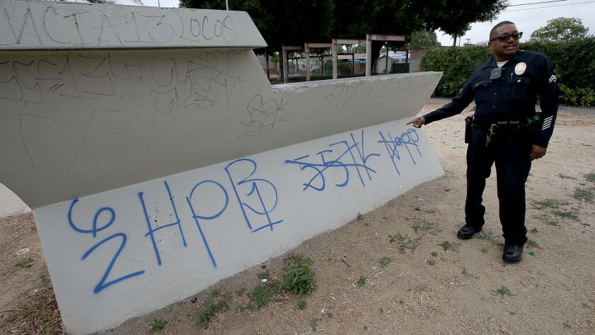 LAPD Senior Lead Officer Gary Verge looks at gang graffiti in Harvard Park in South Los Angeles in this May 2017 file photo.