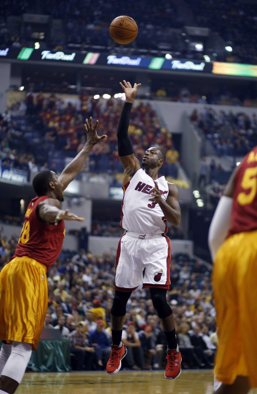 Miami Heat guard Dwyane Wade shoots over the defense of Indiana Pacers center Ian Mahinmi during the first half of an NBA basketball game in Indianapolis, Friday, Nov. 6, 2015. (AP Photo/AJ Mast)